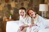 Two kids brother and sister wearing little bathrobes laughing while sitting on bed at hotel room or home