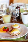 Delicious breakfast with poached eggs and coffee
