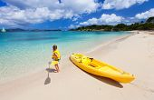Little girl standing next to colorful yellow kayak at tropical beach ready for paddling with her mot