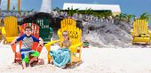 Kids sitting on colorful wooden chairs enjoying vacation at tropical beach in Caribbean