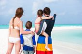Back view of family with two kids in swimming wear at tropical white sand beach during summer vacati