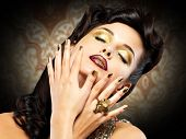 Beautiful brunet woman with golden nails over style background