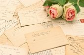 stock photo of nostalgic  - antique french postcards and rose flowers - JPG