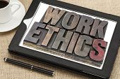work ethics in vintage letterpress wood type on a digital tablet with a cup of coffee