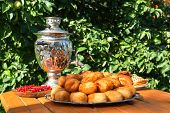 Samovar On A Wooden Table With Cakes And Candies Berries