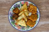 Selection of Indian vegetarian snacks on vintage plate on wooden surface
