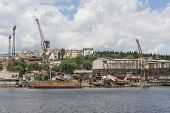 pic of derelict  - Old abandoned derelict dockyards by large river in city - JPG