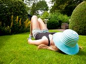 Teenage Girl With A Hat Covering Her Face Lying On Her Back In The Grass