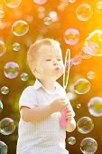 Child blowing a soap bubbles. Boy playing. Kid blowing bubbles on nature. Baby at sunset, the sun's
