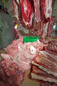foto of pig head  - Heads of dead pigs on display with body parts at the fresh meat market in Puerto Princesa Palawan Philippines - JPG