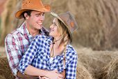 loving young american western couple hugging in barn