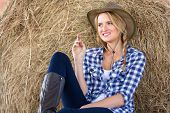 beautiful cowgirl sitting on hay and daydreaming