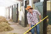 cowboy working in a horse stable