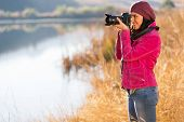 beautiful photographer take photo outdoors by the lake in autumn