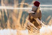 stock photo of hug  - back view of lovely young couple hugging in winter - JPG