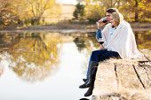 happy couple enjoying spend time together by the autumn lake together