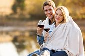image of snuggle  - beautiful young couple snuggle outdoors with glass of wine - JPG