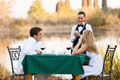 beautiful young couple place dinner order to waitress outdoors