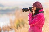happy female photographer taking photos outdoors in fall