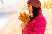 side view of happy young woman holding autumn leaves