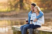 young couple relaxing outdoors having red wine