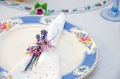 foto of dainty  - Dainty nosegay napkin ring with bow tied around linen napkin on a dinner plate - JPG