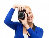 modern technology and people concept - smiling woman in casual clothes taking picture with digital c