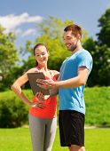 fitness, sport, friendship, technology and lifestyle concept - smiling couple with tablet pc compute