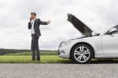 Young businessman using cell phone by broken-down car at countryside