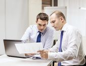 business, technology and office concept - two businessmen with laptop, tablet pc computer and papers