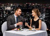 restaurant, couple and holiday concept - smiling couple eating main course with red wine at restaura