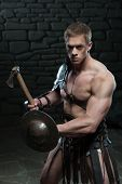 image of sparta  - Half length portrait of young attractive warrior gladiator with muscular body holding shield and axe, defending on dark background. Concept of masculine power, strength