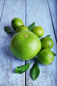 pic of sweetie  - Ripe sweetie and limes on wooden background - JPG