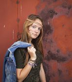 Portrait of a young pretty hippie-girl on a background of metallic red wall.