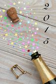 Champagne cork pop with the date 2015 on a rustic wood surface. Metallic star simulate the spray from a bottle being opened.