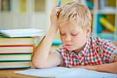 Pensive little boy looking at page of his copybook at lesson