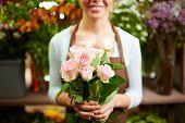 Female holding bunch of pale roses