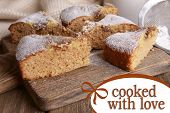 Pieces of delicious cake on cutting board on wooden table with space for text
