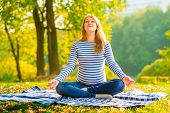 Pregnant Woman In A Lotus Position Performs Breathing Exercises Outdoors