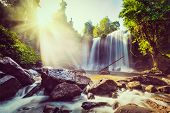 Vintage retro effect filtered hipster style image of tropical waterfall with sun rays in Cambodia