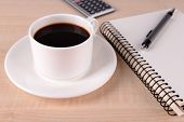 Cup of coffee on saucer with notebook, calculator and pen on wooden table background