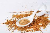 Mustard powder in spoon on mustard seeds, on  wooden background