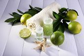 Spa composition with lime and towel color wooden background