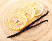 Dried slices of lemon with vanilla beans on wooden background