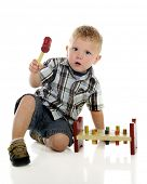 A young preschooler looking concerned about using the mallet on a classic wooden hammer and peg toy.  On a white background.