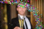 picture of champagne color  - Handsome man holding flute of champagne against colour curve - JPG