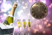 Clock counting down to midnight against champagne cooling in ice bucket