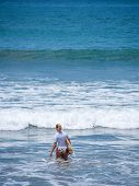 Beautiful young woman surfing in Kuta Bali