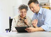 Man with elderly woman using digital tablet
