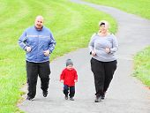 Overweight parents with her son running together. Weight loss concept.